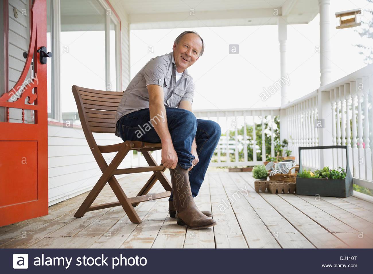 L'homme tirant sur bottes de cow-boy Photo Stock