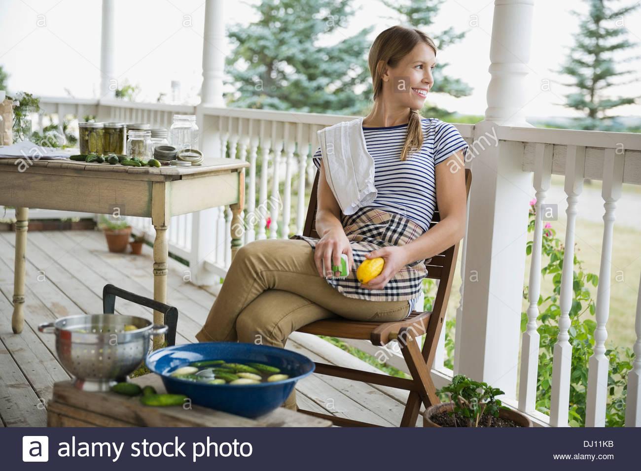 Jeune femme laver les légumes sur le porche Photo Stock