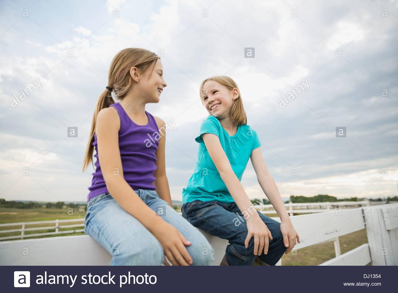 Smiling sisters sitting sur main courante à l'un l'autre Photo Stock