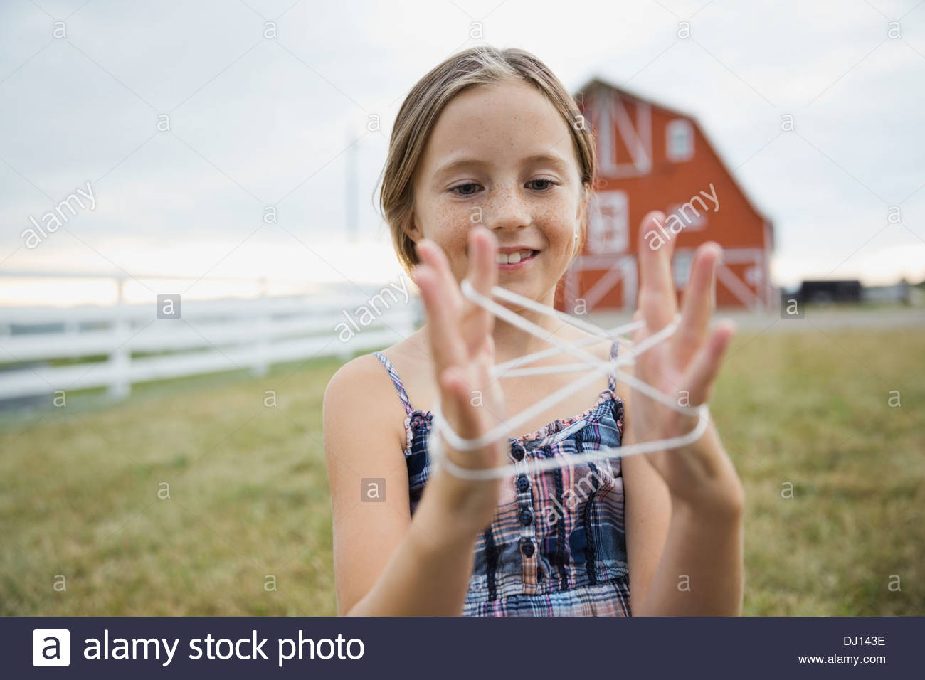 Young Girl playing cats cradle on farm Photo Stock