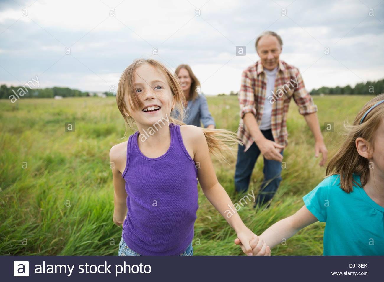 La chasse des grands-parents-enfants dans le champ Photo Stock