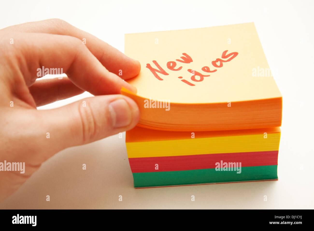 La main de l'homme en tenant un papier de notes dans le bloc de nouvelles idées Photo Stock