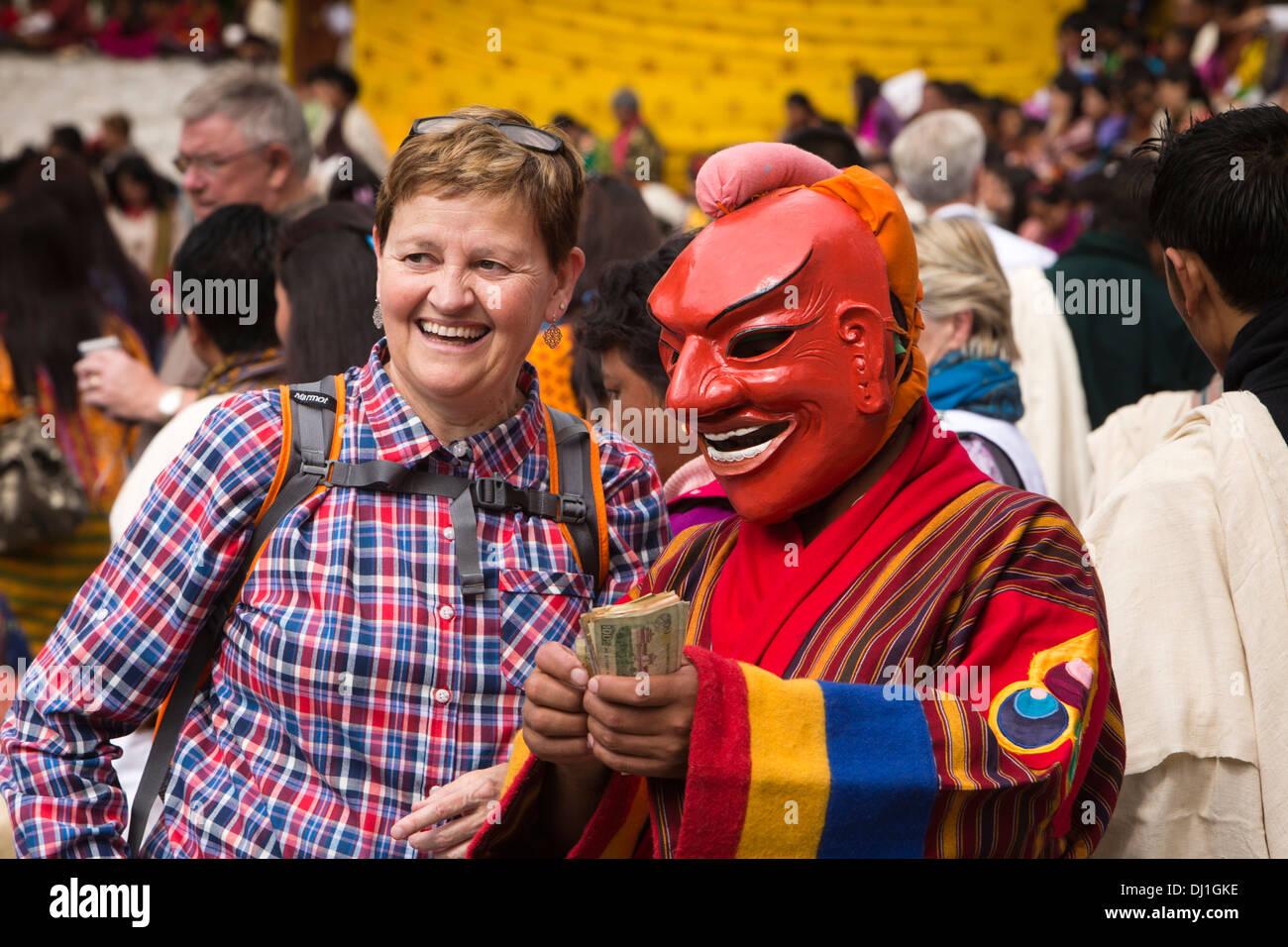 Le Bhoutan, Thimphu Dzong, Tsechu annuel touristique de l'ouest féminin avec atsara danseur clown holding d'argent dans la main Photo Stock