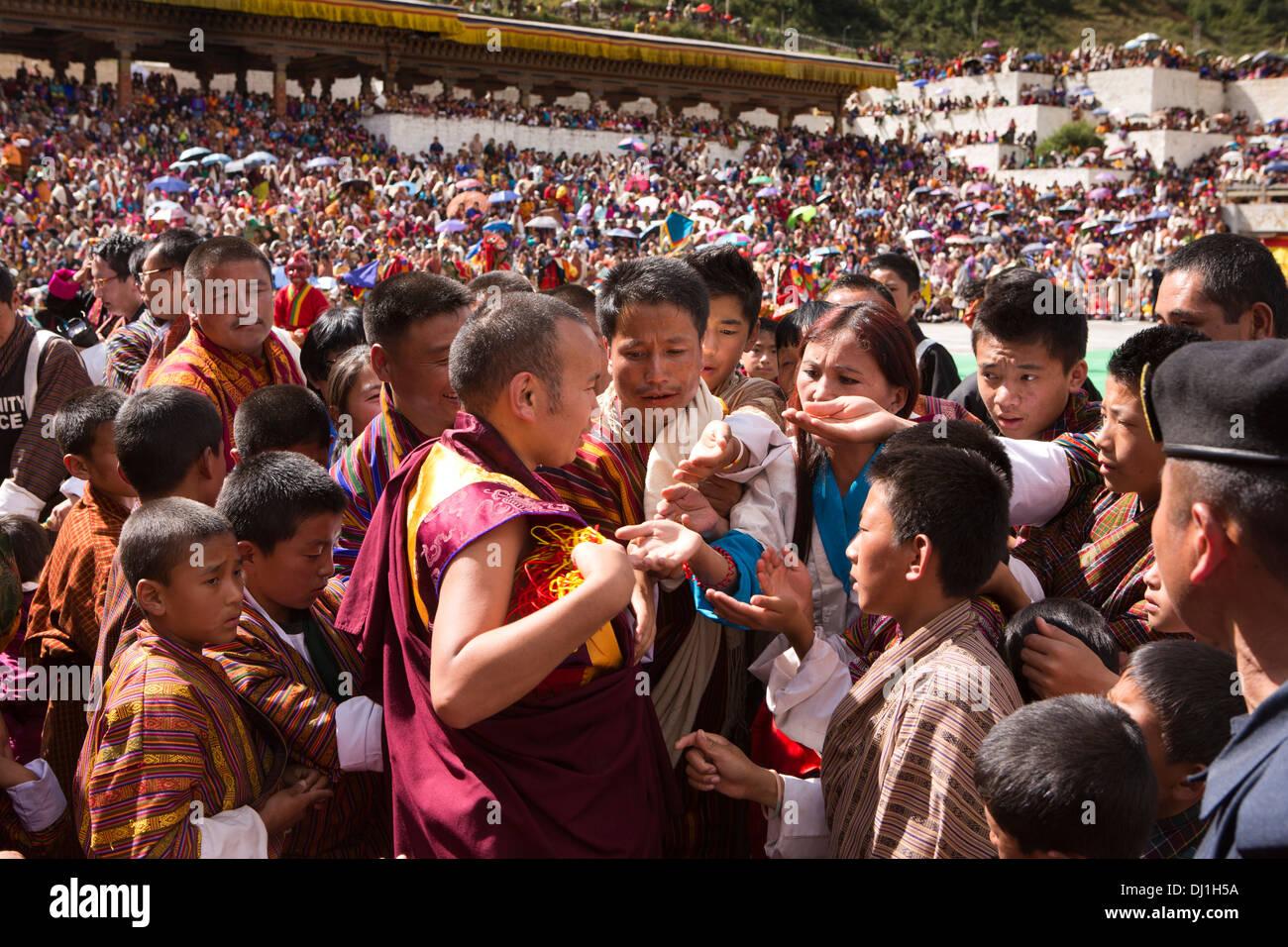 Le Bhoutan, Thimphu Dzong, Tsechu annuel foule à la recherche de bénédiction de couleur de fils de moine Photo Stock
