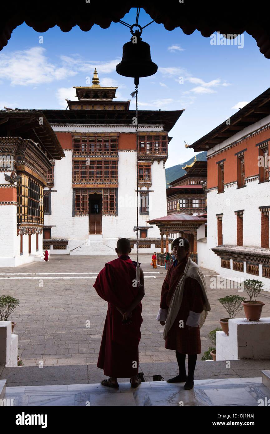 Le Bhoutan, Thimphu Dzong, deux hommes en tenue habillée en cour sous bell, silhouette Photo Stock