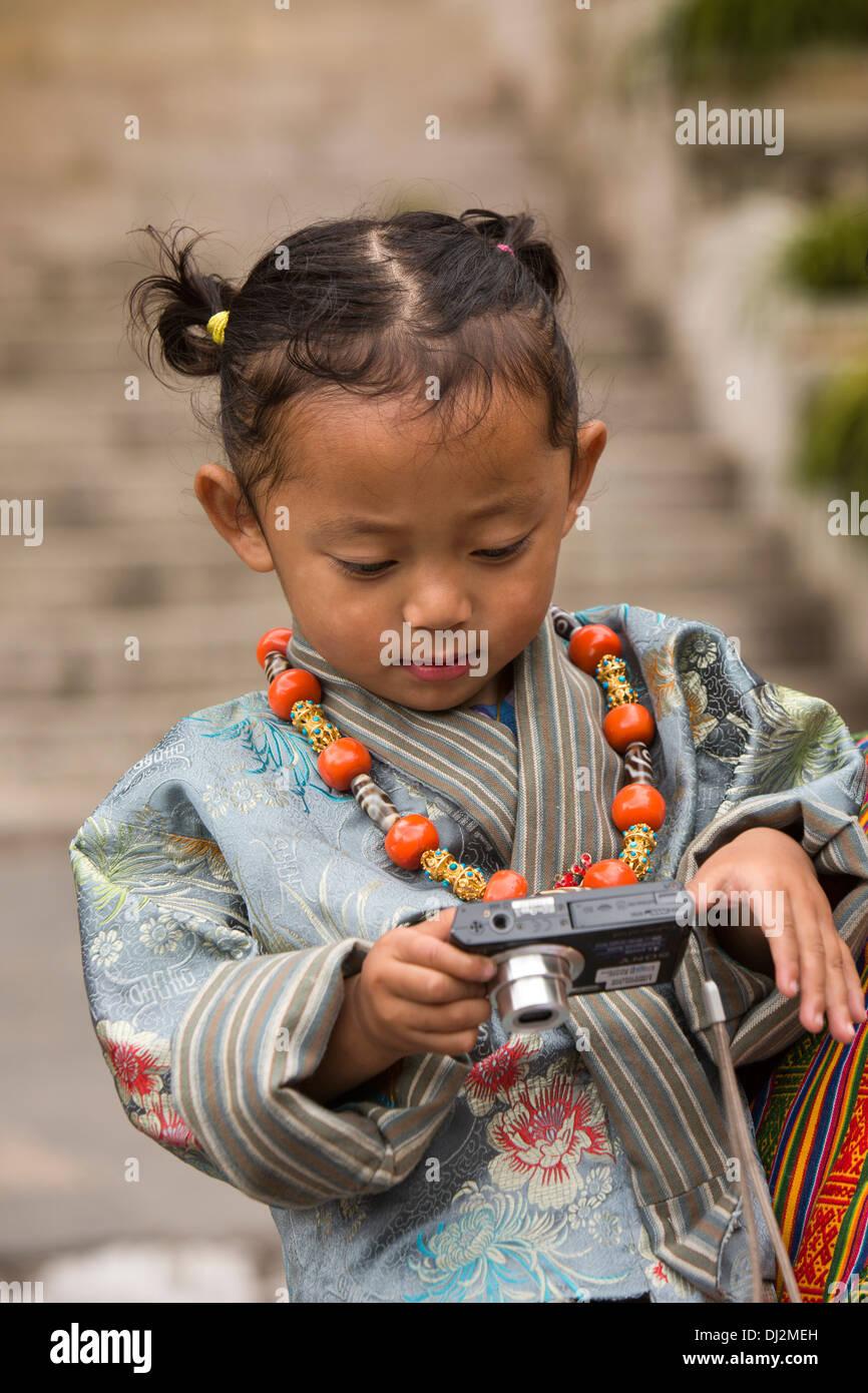 Le Bhoutan, Thimphu Dzong, Tsechu annuel, jeune fille dans les bras du père avec appareil photo numérique Photo Stock