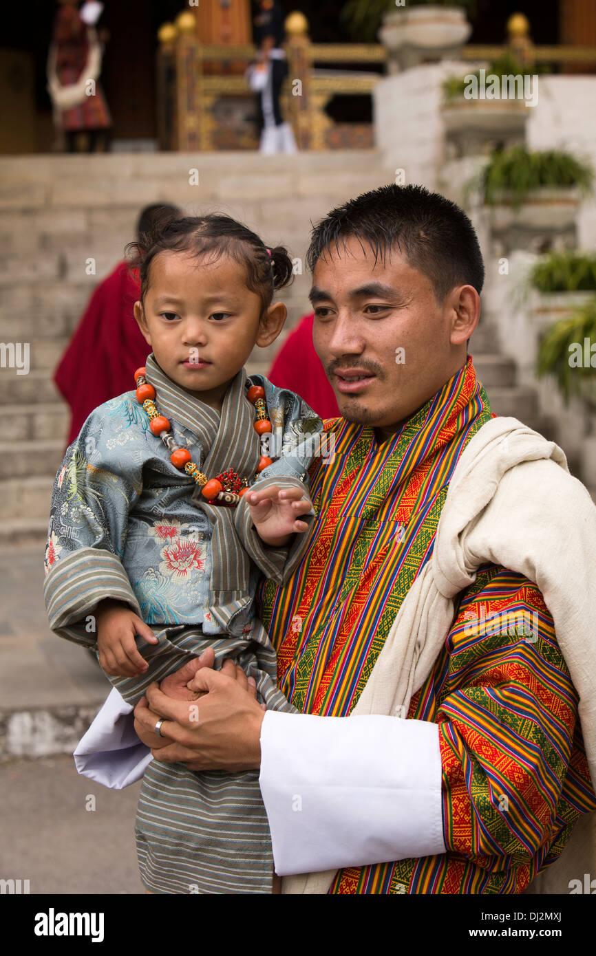 Le Bhoutan, Thimphu Dzong, Tsechu annuel, traditionnellement vêtus jeune fille dans les bras du père Photo Stock