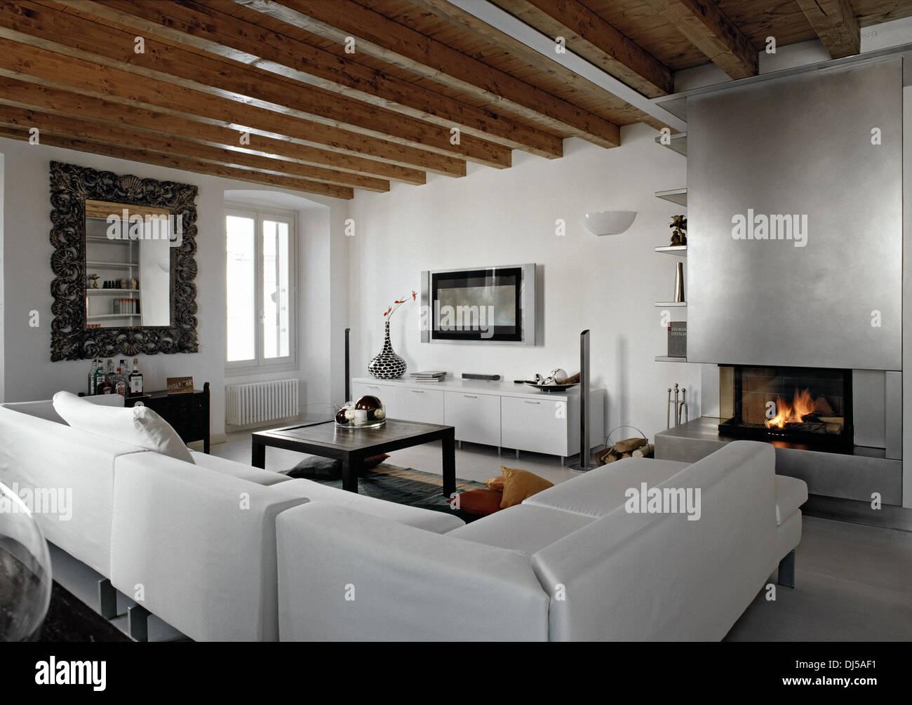 Canapé en tissu dans un salon moderne avec cheminée et plafond en ...