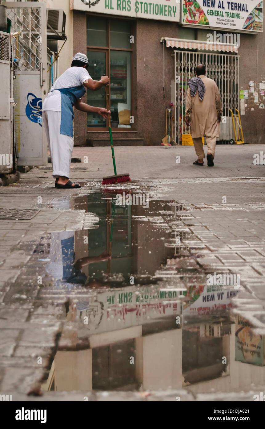 Un greffier balaie la chaussée mouillée à l'extérieur de son magasin dans les rues de Deira. Dubaï, Émirats arabes unis. Photo Stock