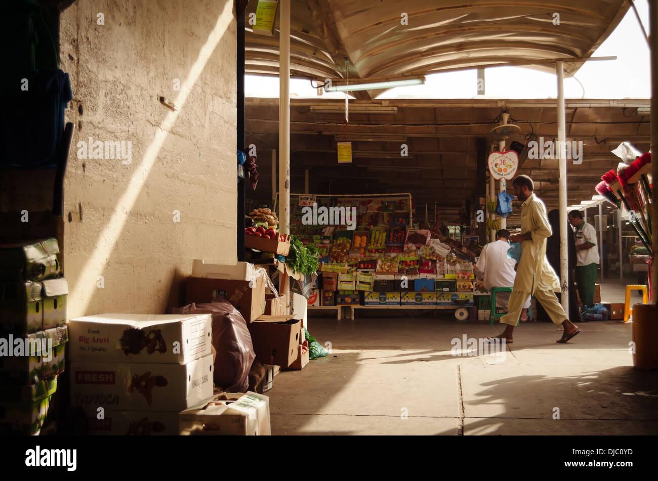 Un homme marche le long d'un des pays arabes les couloirs du Deira au marché de fruits et légumes. Photo Stock