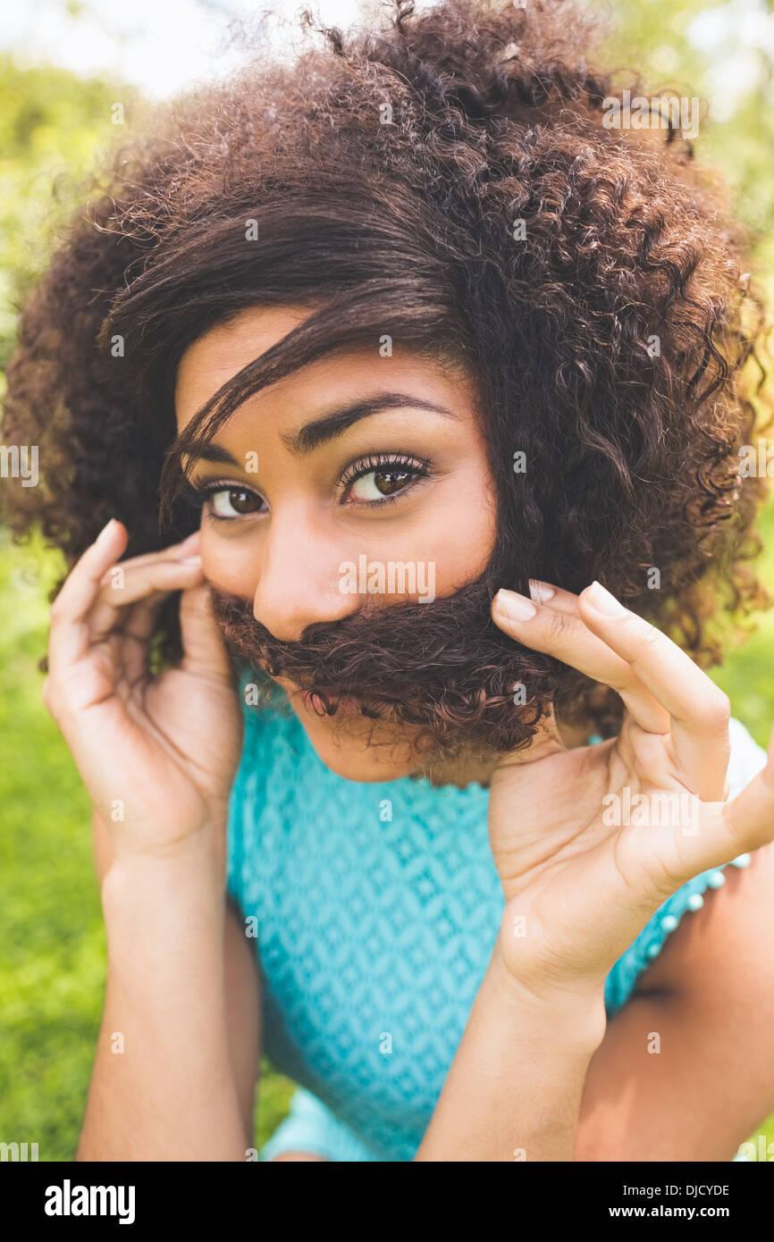 Gorgeous brunette heureux prétendant qu'elle a une moustache Photo Stock