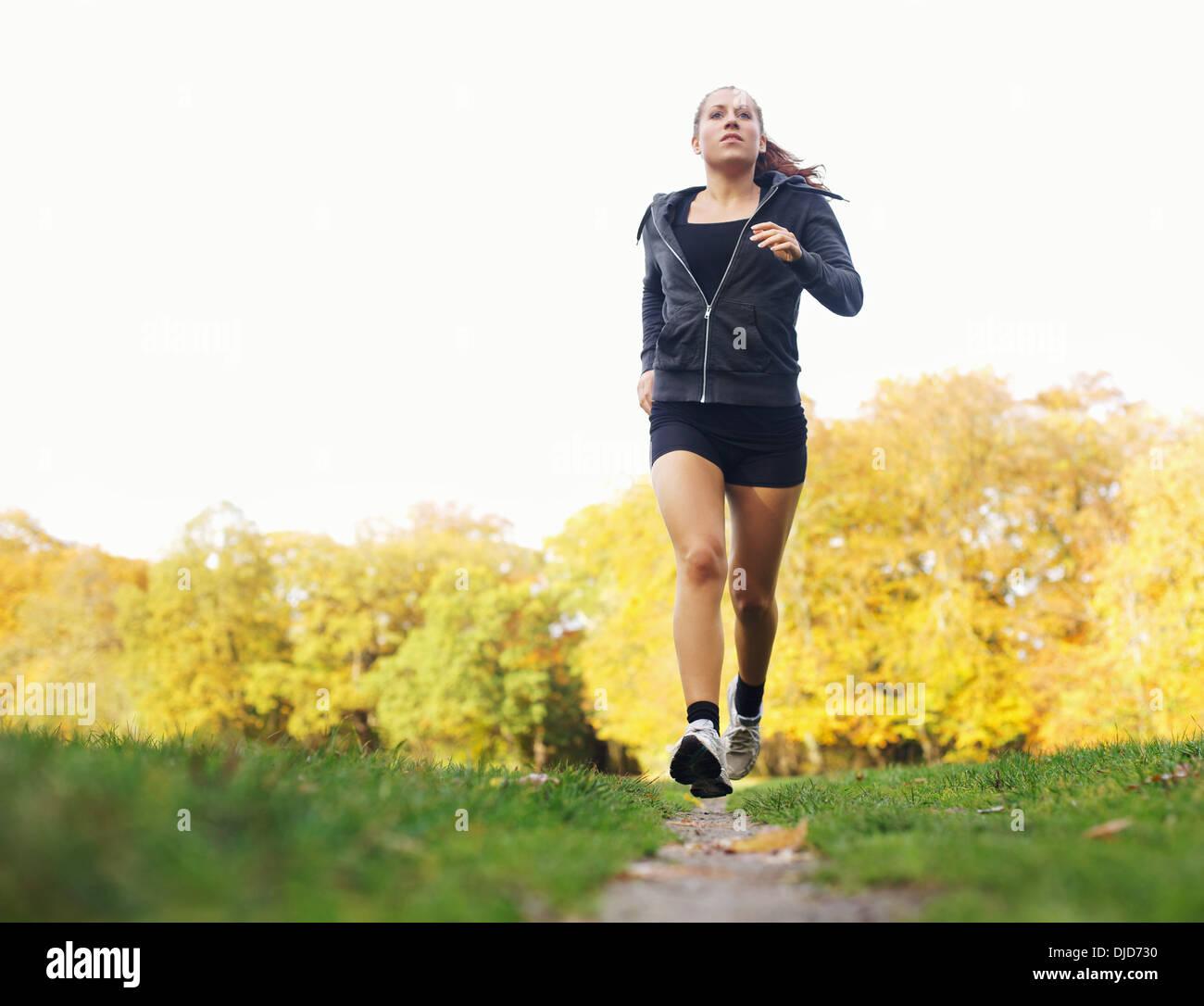 Longueur totale de droit d'une jeune femme jogging en parc. Athlète féminine caucasienne runner d'exécution. La formation de remise en forme dans la nature. Photo Stock