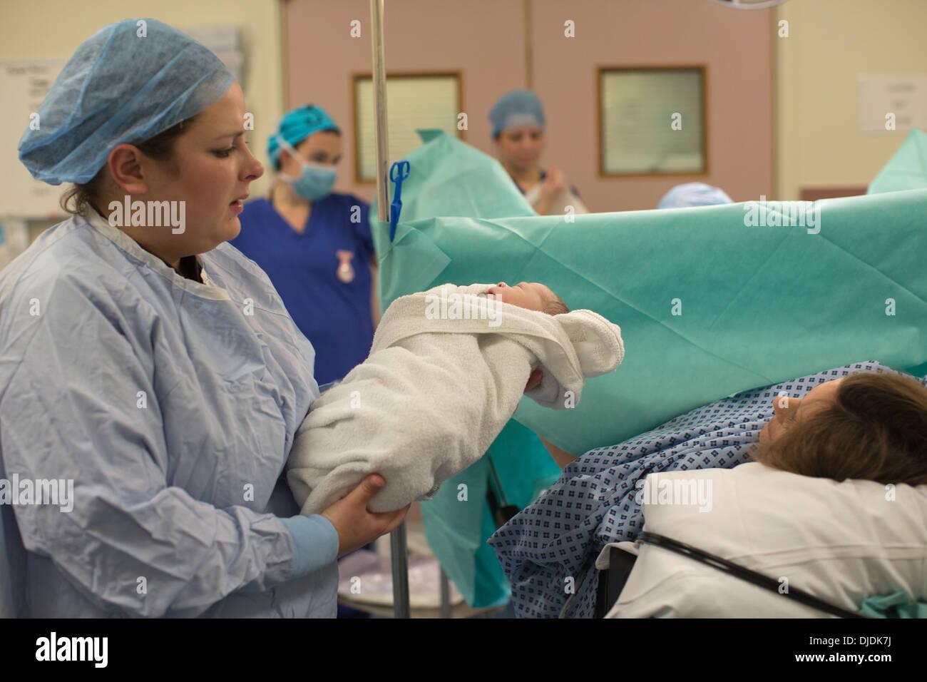 Bébé nouveau-né garçon d'être vérifié par des infirmières à l'hôpital théâtre de la maternité sur la salle de travail à l'hôpital, Kingston Upon Thames, Royaume-Uni Photo Stock
