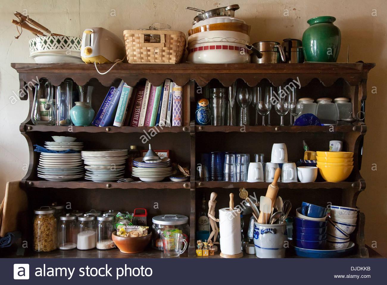 Étagères en désordre dans la cuisine pleine de livres de cuisine, des plats et des aliments, Photo Stock
