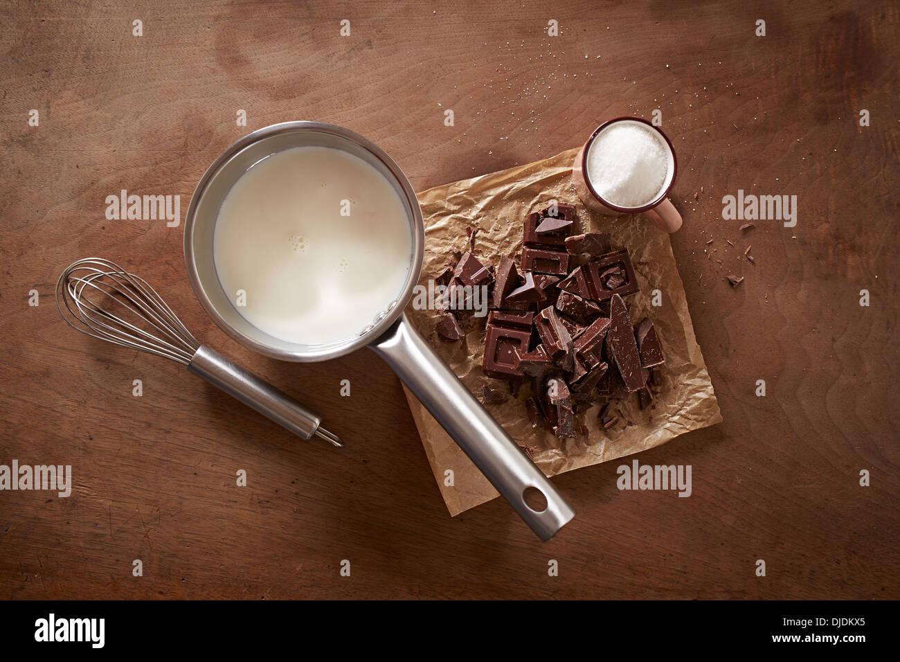 Chocolat chaud au lait ingrédients sur table en bois donnent sur shot Photo Stock