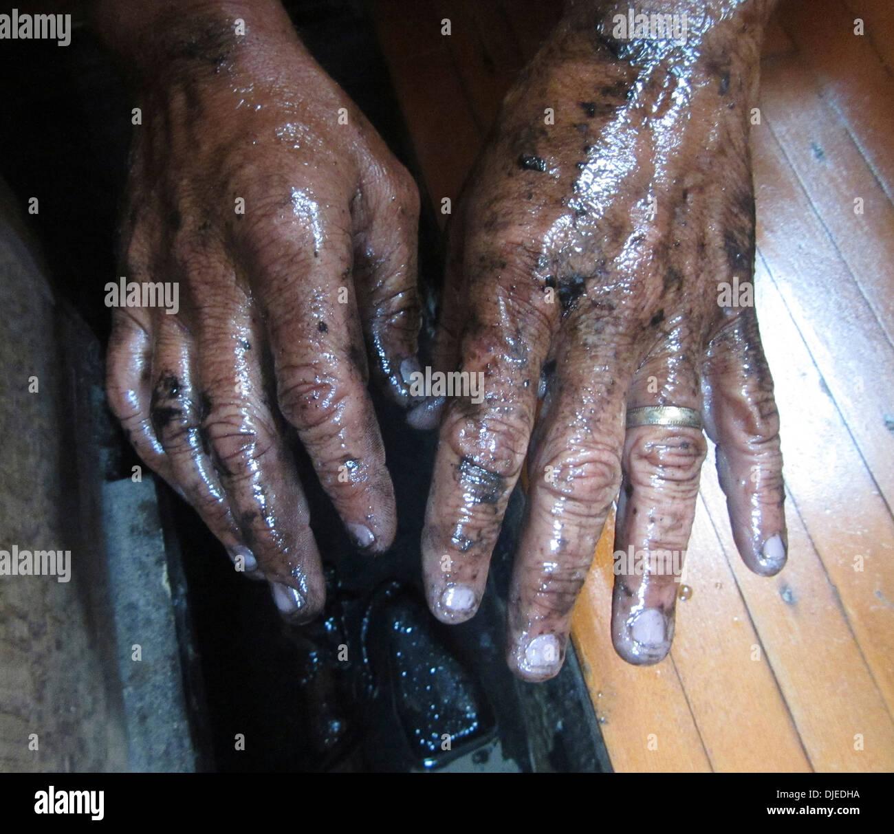 Les mains sales, gras, qui ont été dans la cale d'un bateau fuite d'huile. Photo Stock