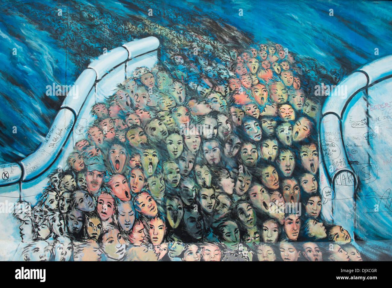 L'art du graffiti représentant les personnes fuyant Berlin Est. Peint sur la East Side Gallery, Berlin, Allemagne. Photo Stock