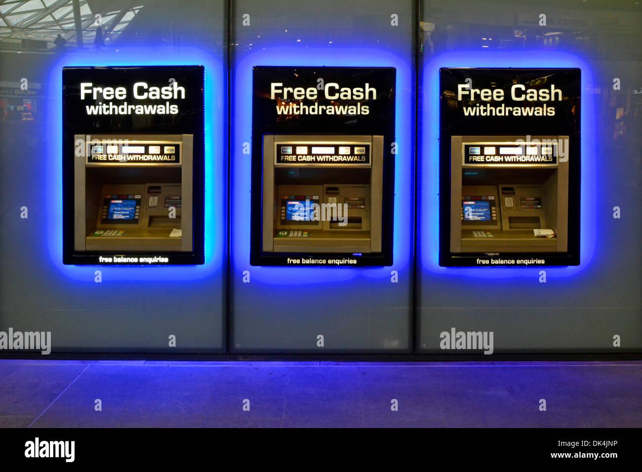 La gare s'allume en bleu autour de la rangée de trous d'argent du distributeur automatique de billets Dans le mur distributeur d'argent machine Kings Cross train Station Londres Angleterre Royaume-Uni Banque D'Images