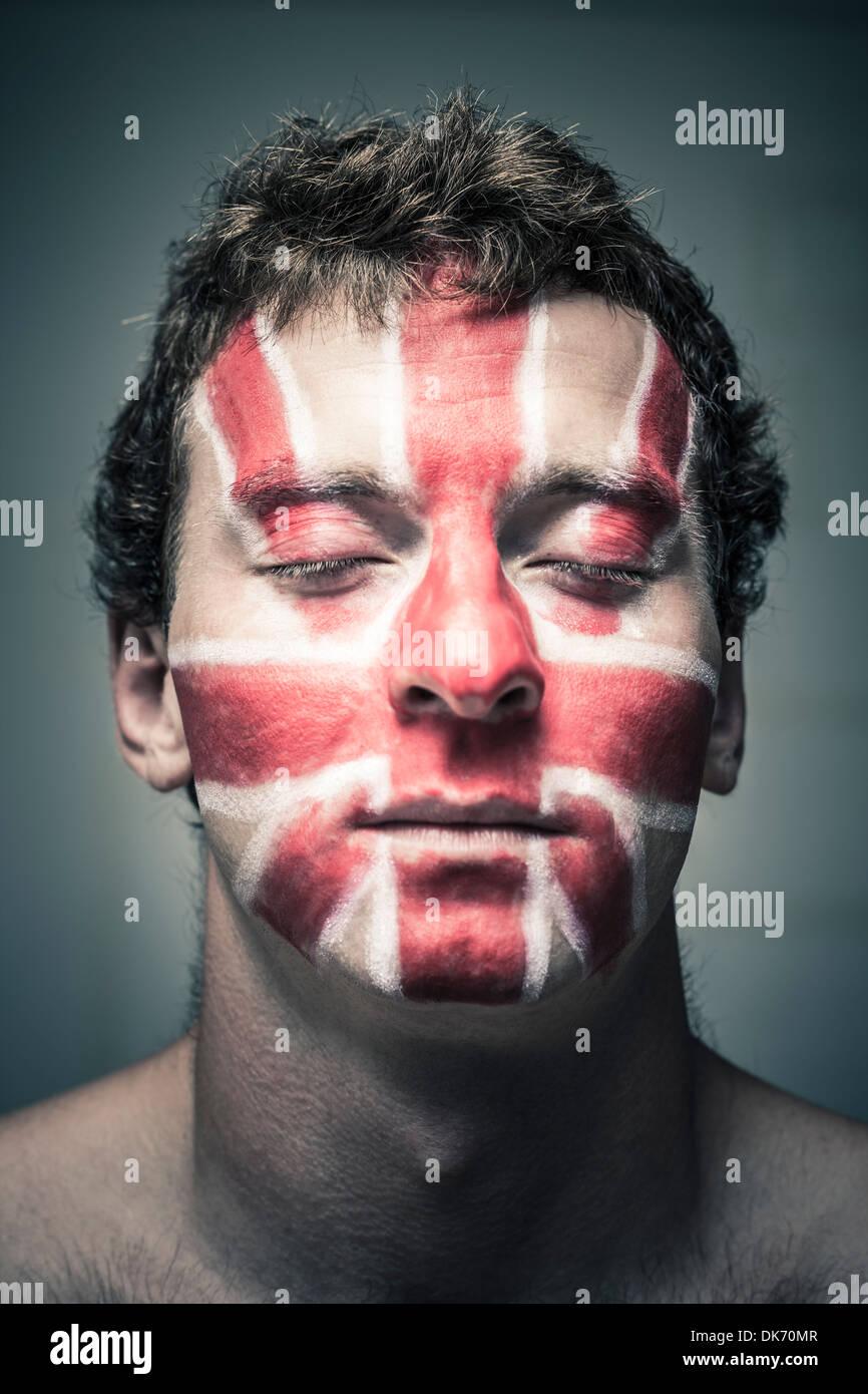 Portrait d'homme avec drapeau anglais peint sur son visage et ferma les yeux. Photo Stock