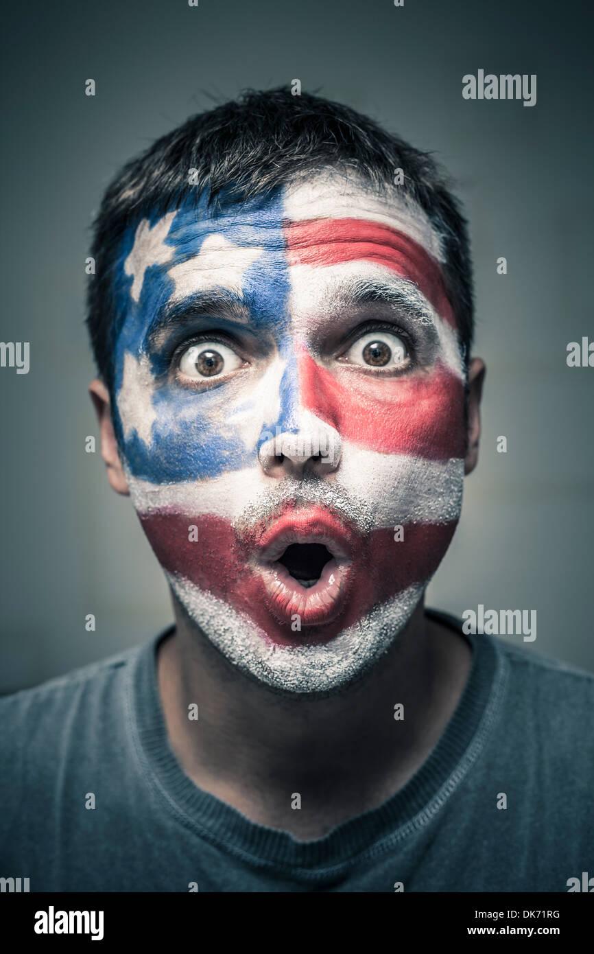 Portrait de l'homme surpris avec drapeau américain peint sur la face. Photo Stock