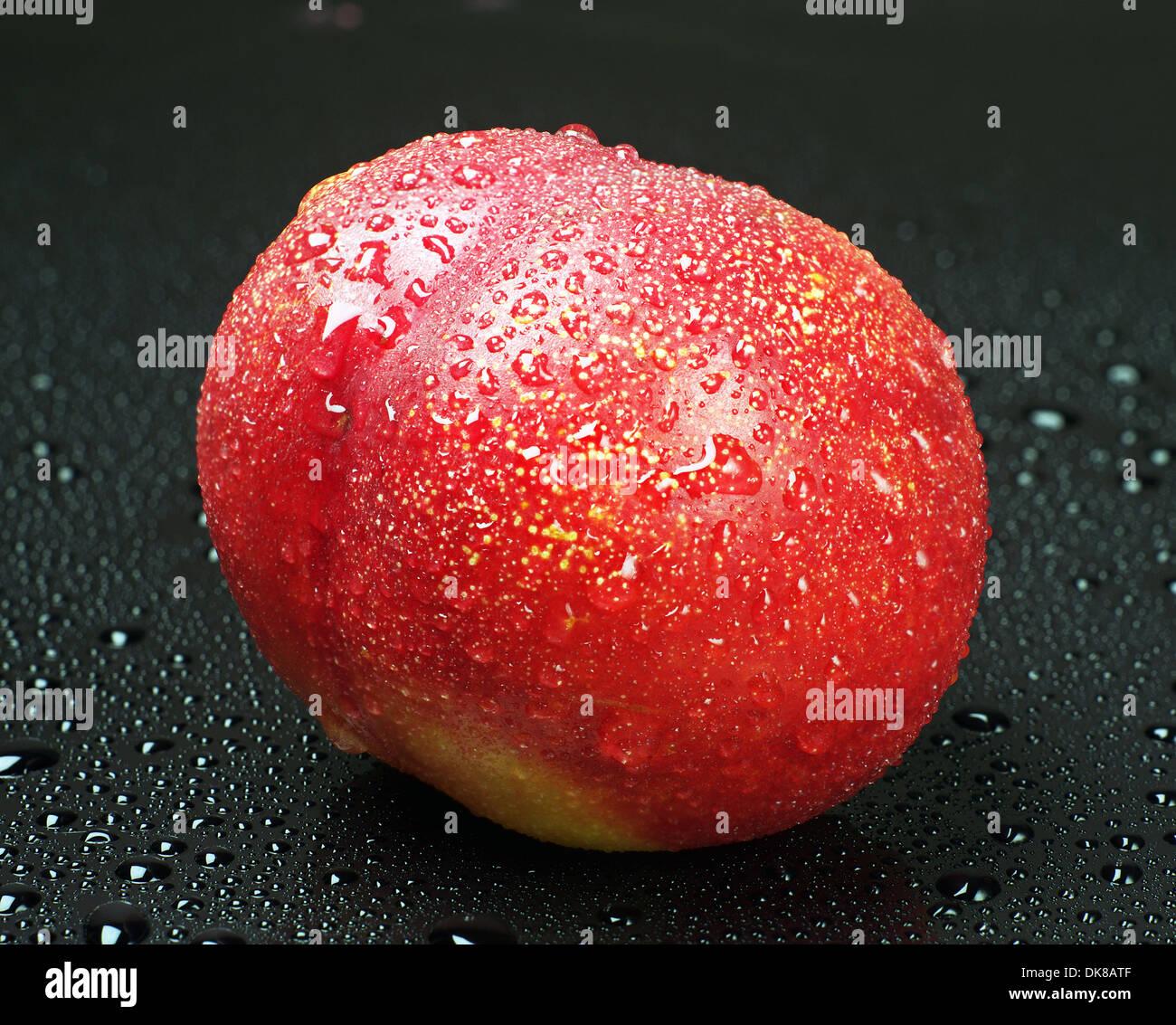 Nectarines avec de l'eau tombe sur noir Photo Stock