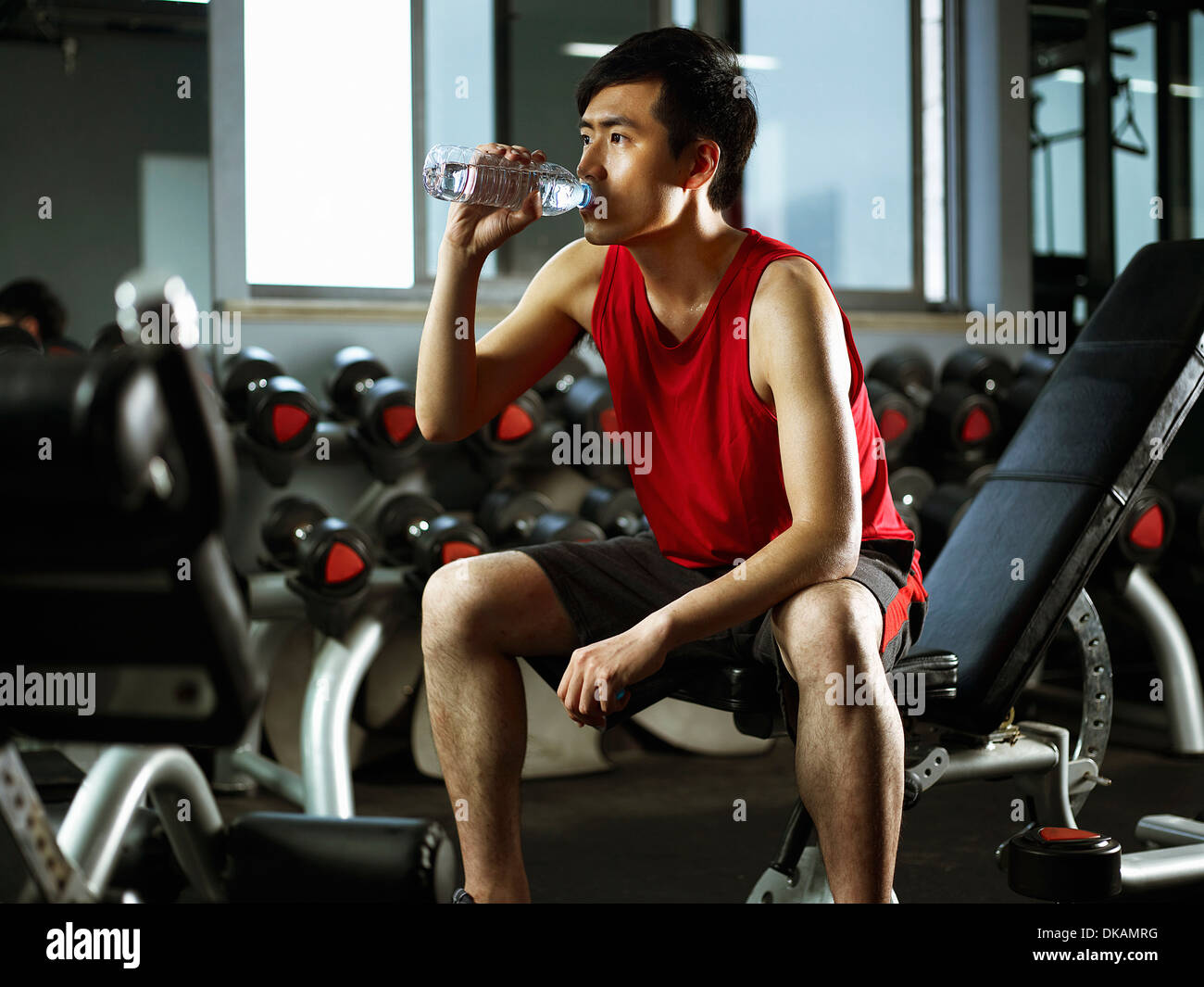 Homme assis sur banc poids bouteille d'eau potable Photo Stock