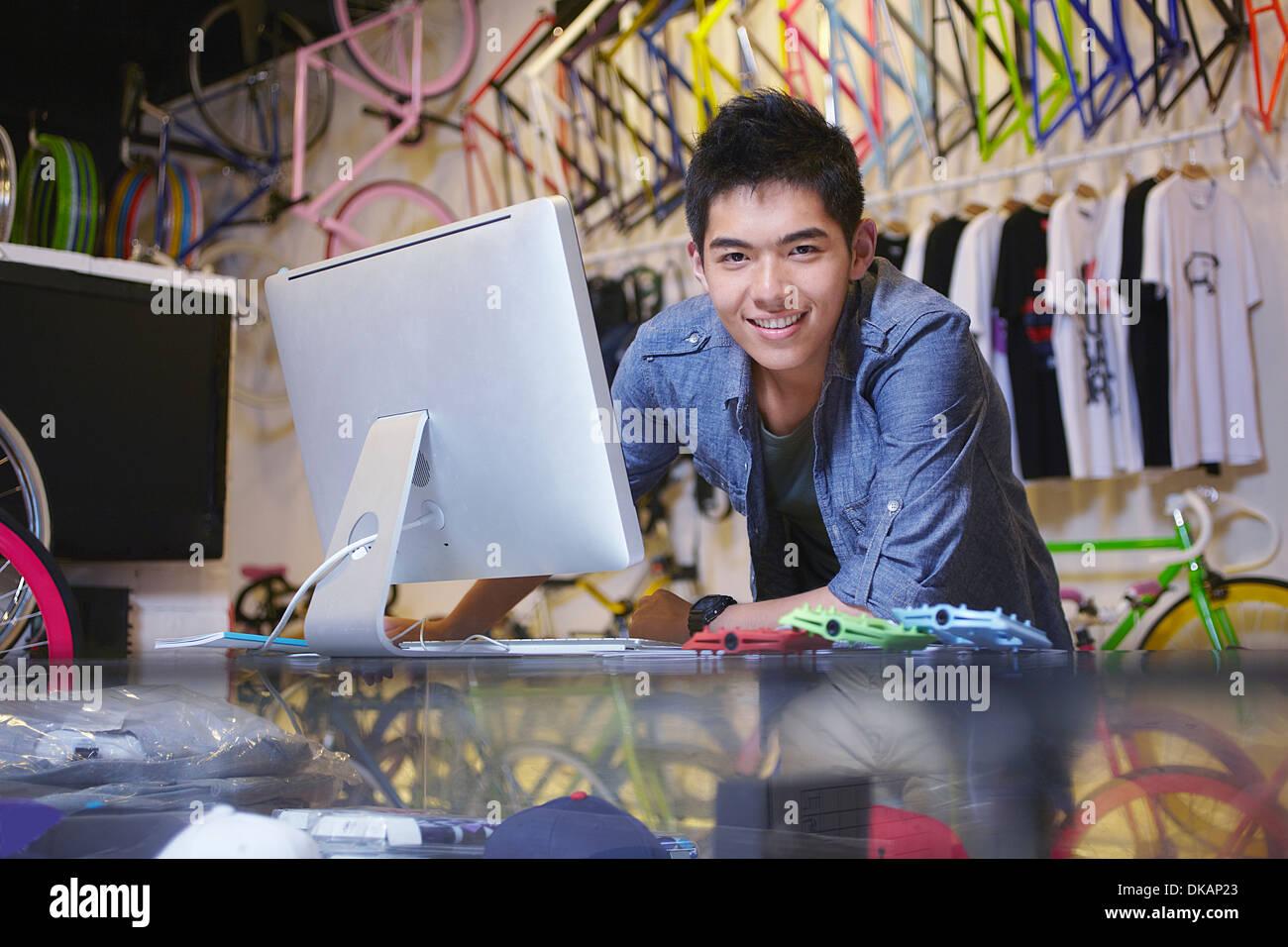 Jeune homme dans le magasin de vélo à l'aide d'ordinateur Photo Stock