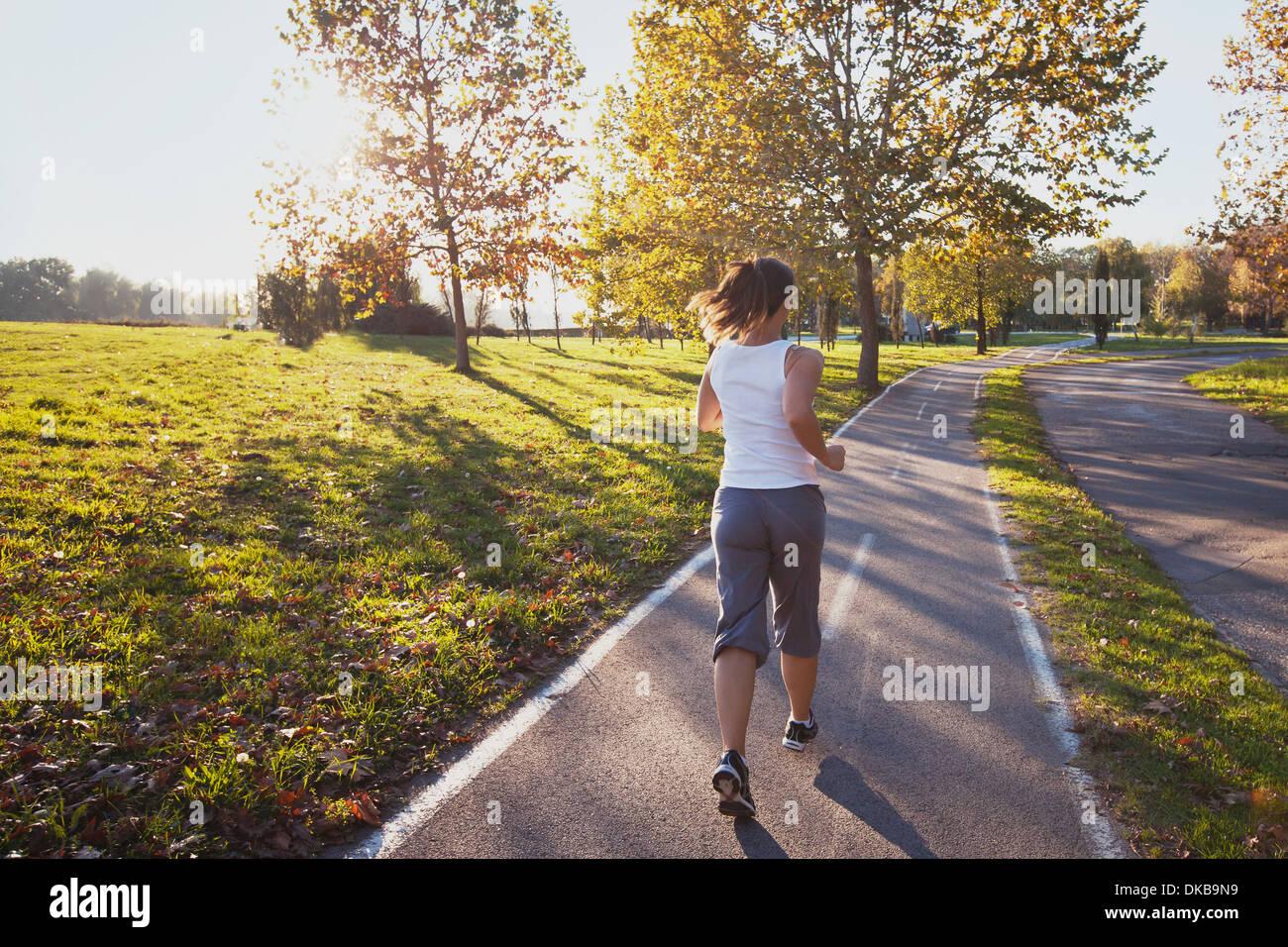 Femme courir dans le parc, l'arrière-plan de remise en forme Photo Stock