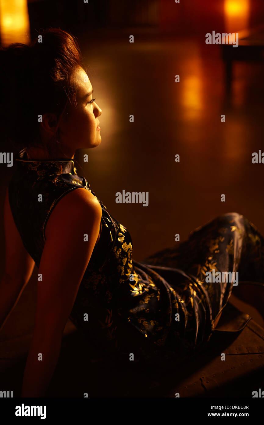Jeune femme assise dans une pièce sombre, Banque D'Images