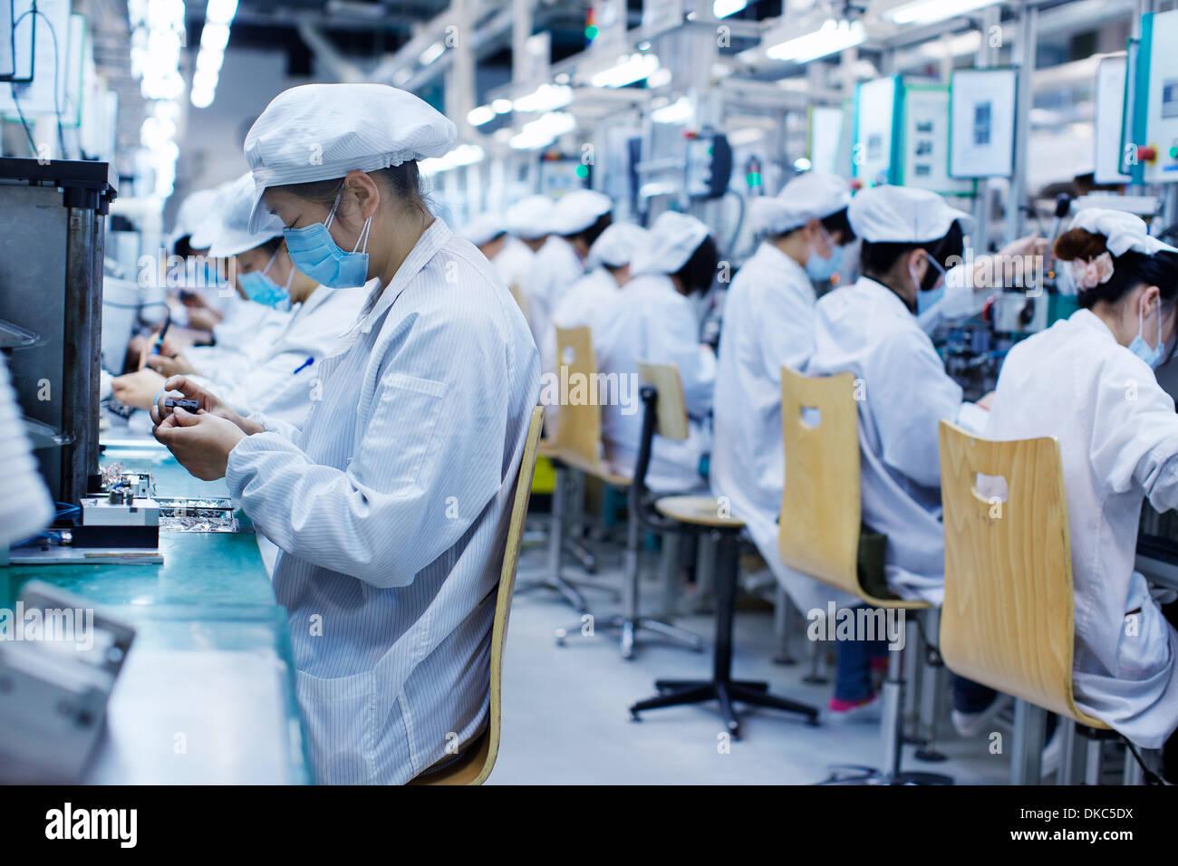 Groupe de travailleurs à l'usine de fabrication de petites pièces en Chine, portant des vêtements, des chapeaux et des masques Photo Stock