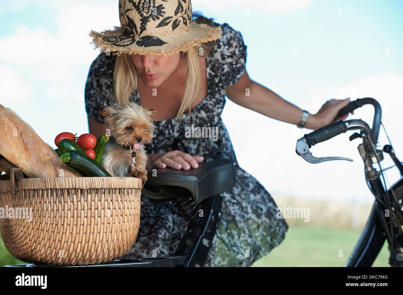 Femme mature sur vélo électrique avec chien et les légumes dans le panier Photo Stock
