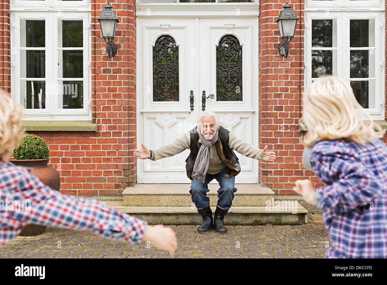 Grand-père avec ses petits-enfants accueillant les bras ouverts Photo Stock