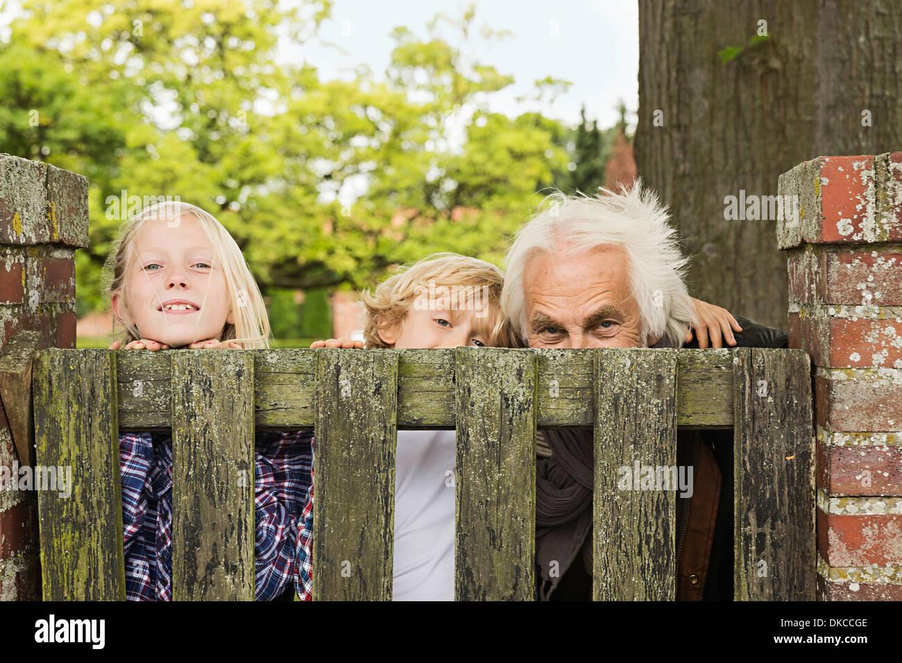 Grand-père et ses petits-enfants sur plus de barrière en bois Photo Stock