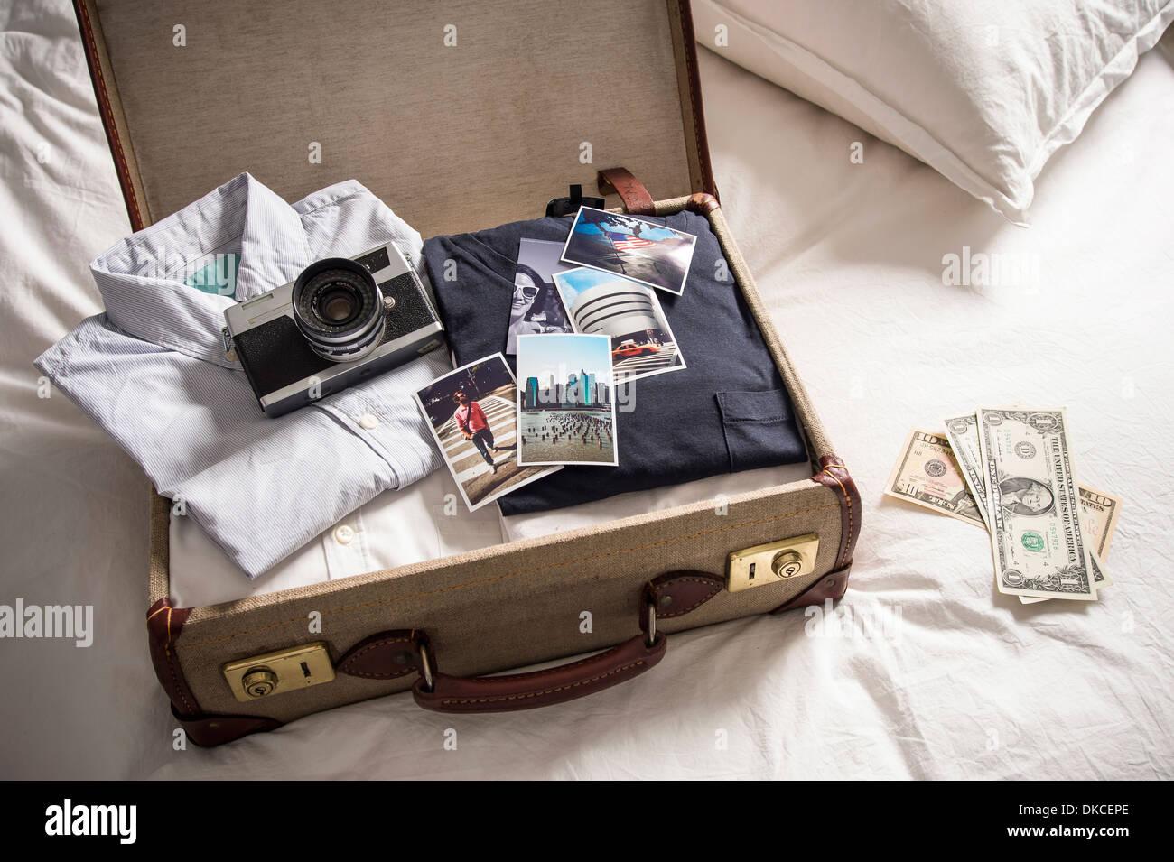 Valise ouverte sur le lit avec l'appareil photo et les photos Photo Stock