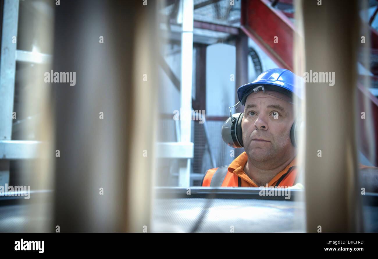 Worker in hard hat et oreilles inspection sable de zircon Photo Stock