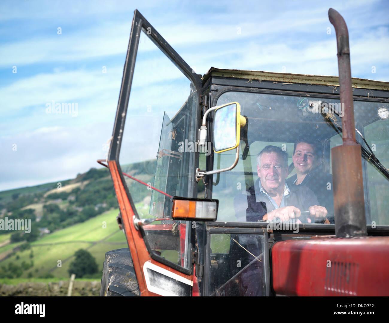 Agriculteur et son fils dans la cabine du tracteur, portrait Photo Stock