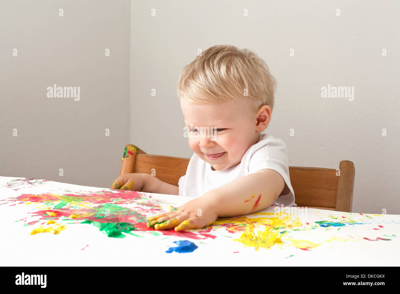 Petit Garçon jouant avec les peintures au doigt Photo Stock