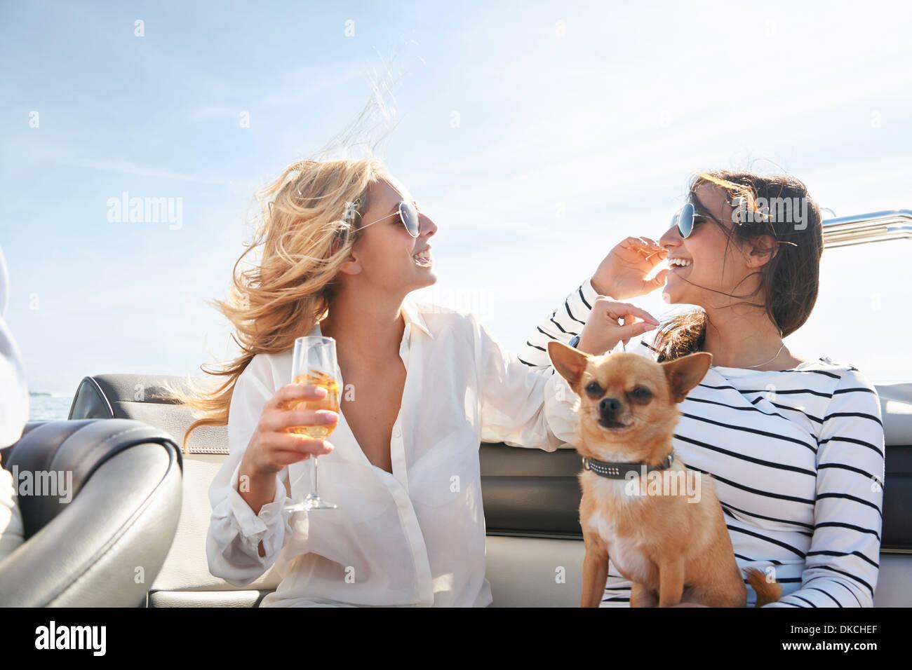 Les jeunes femmes sur le bateau avec du vin Photo Stock