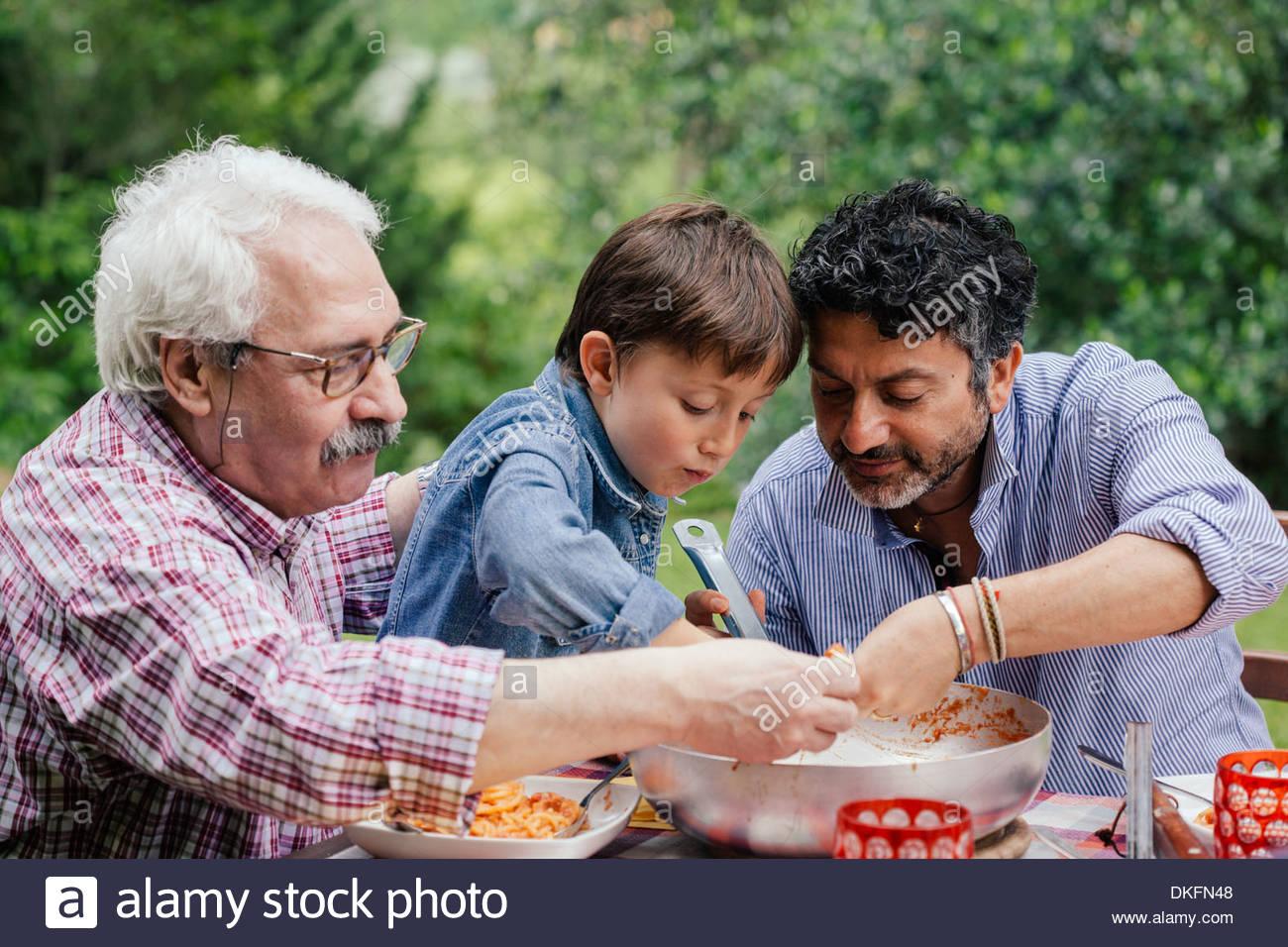 Trois générations d'hommes de la famille appréciant un repas ensemble Photo Stock