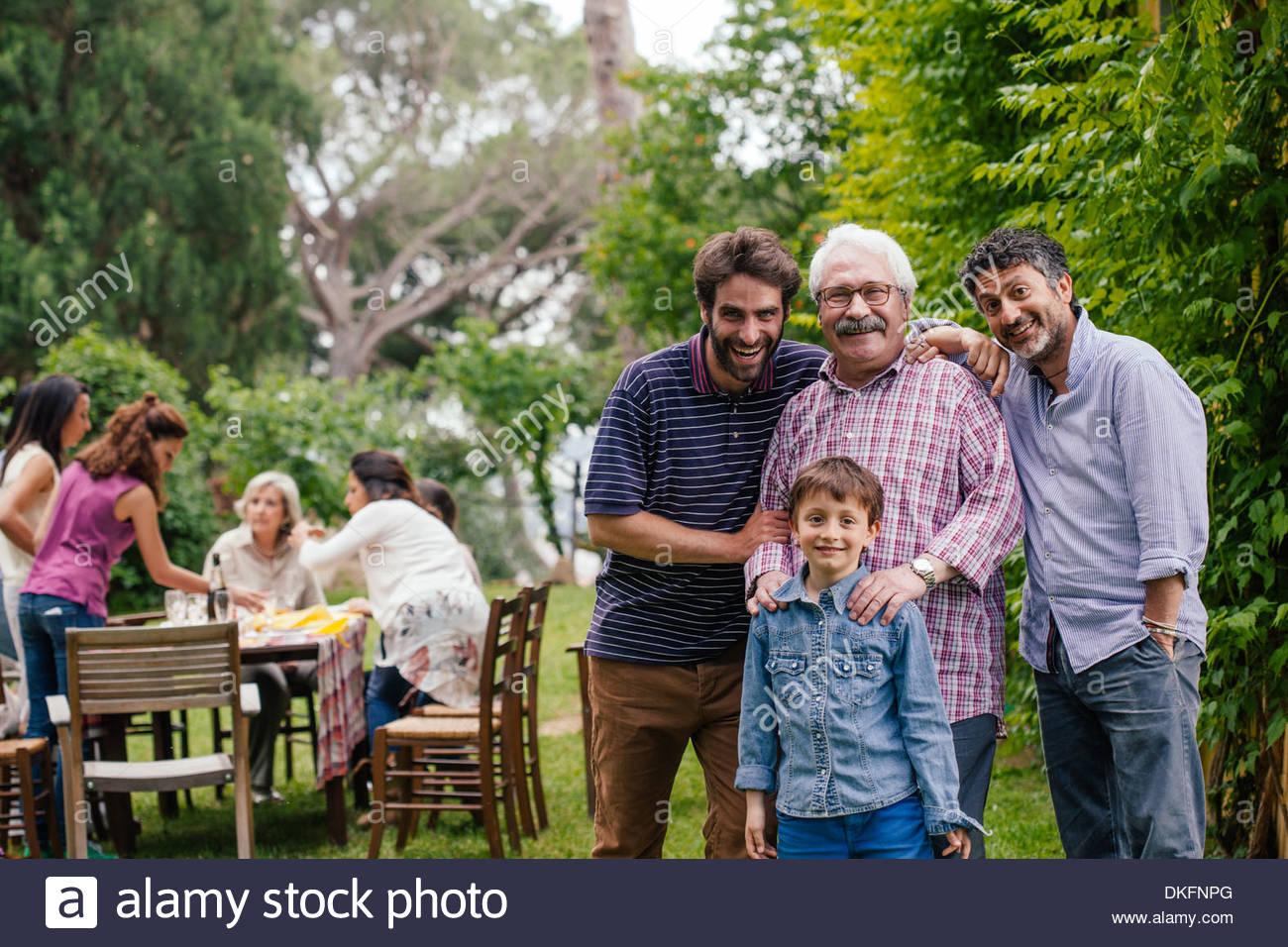 Famille à la rencontre de jardin - les membres masculins de la famille en premier plan, les femmes de la famille à table en arrière-plan Photo Stock