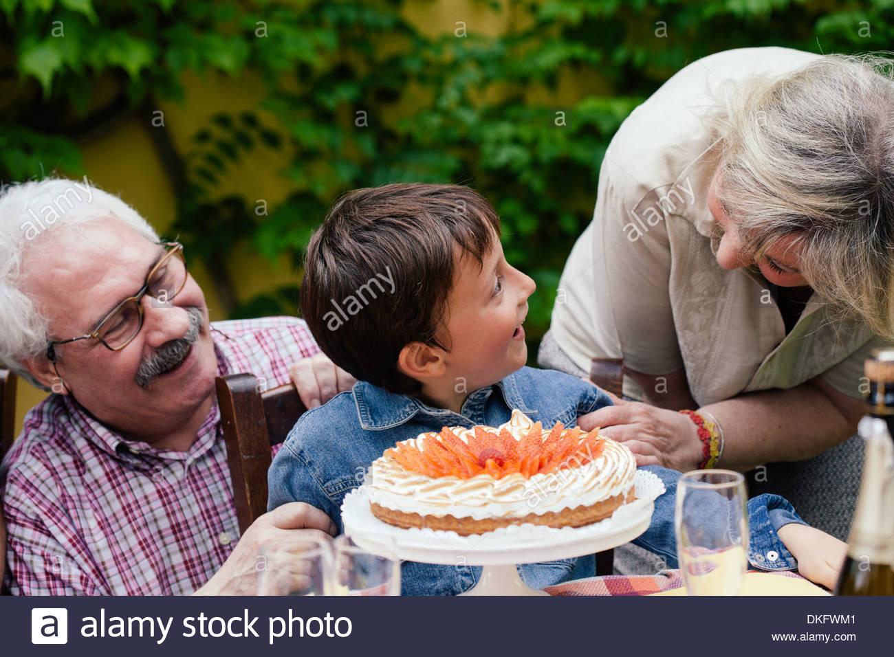 Les grands-parents étonnant petit-fils avec gâteau d'anniversaire Photo Stock
