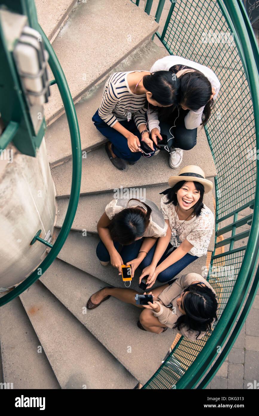 Cinq jeunes femmes assis sur les marches à smartphones à Photo Stock