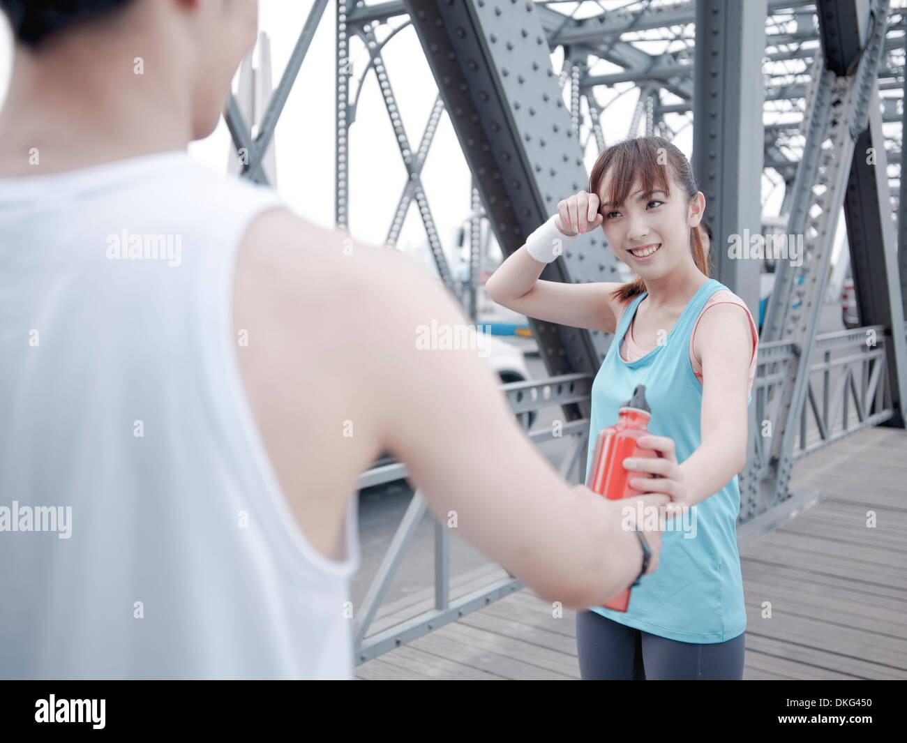 Homme jogger passage de l'eau bouteille pour compagne Photo Stock
