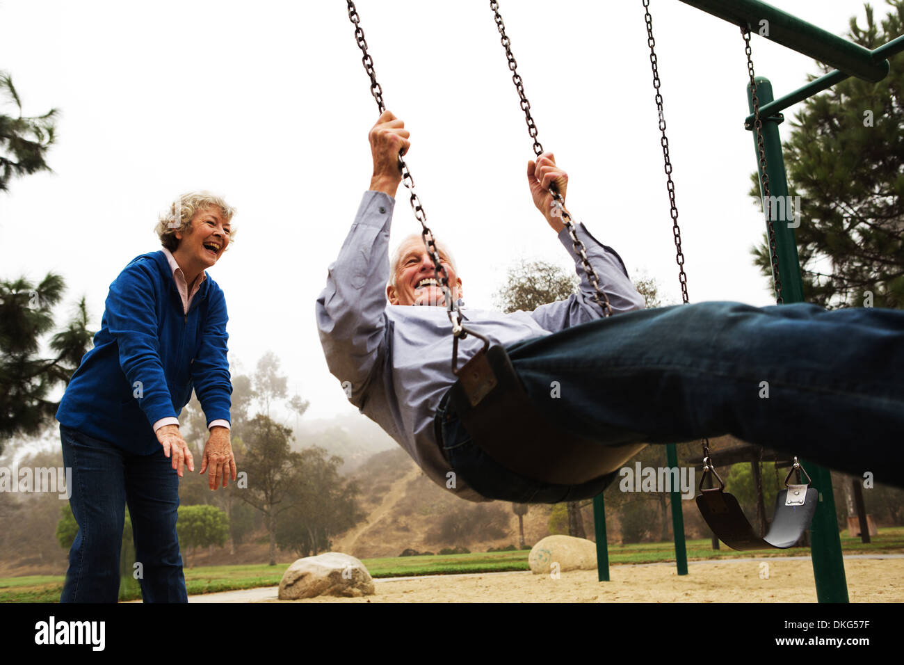 Femme poussant mari on swing Photo Stock