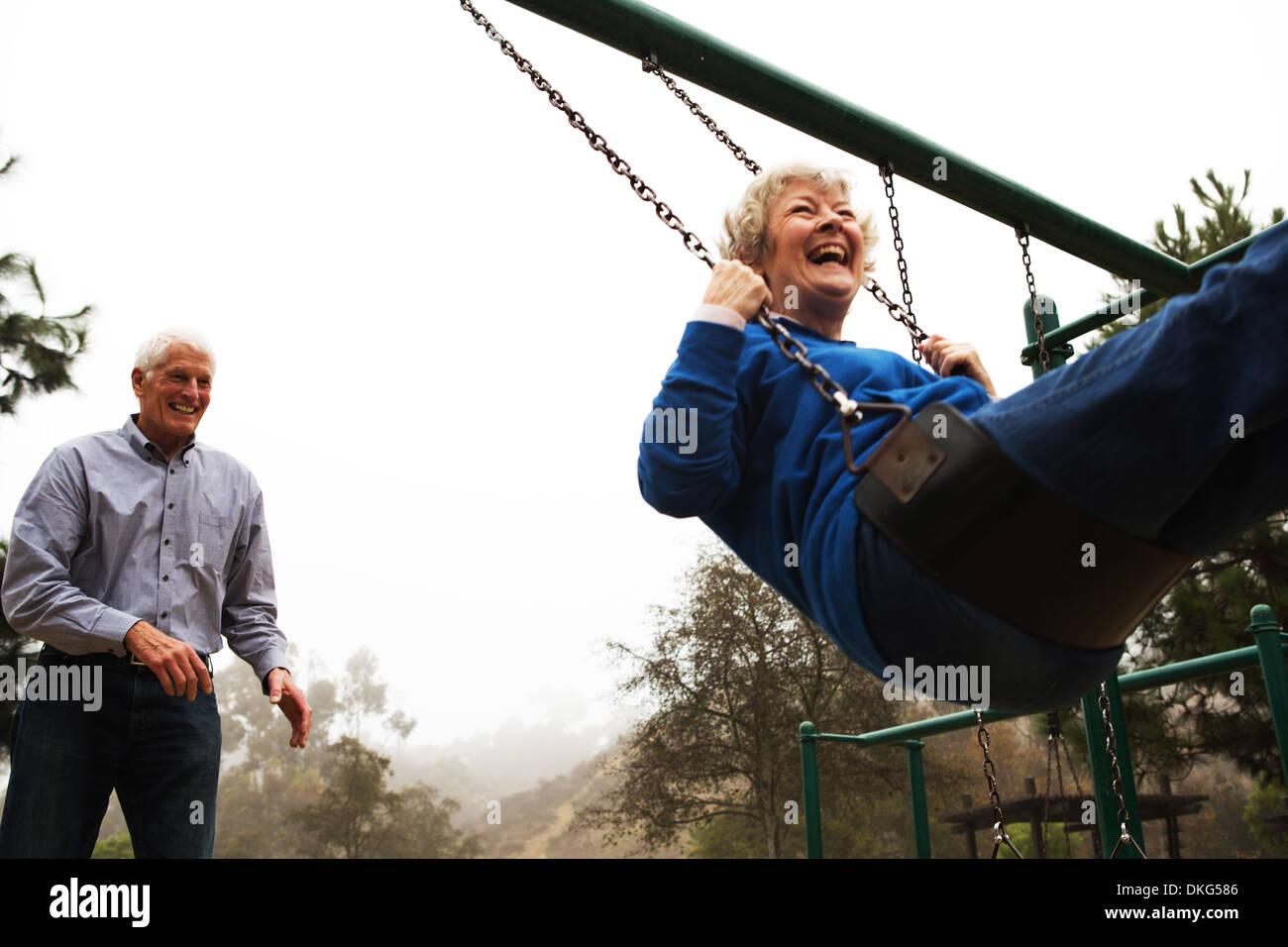 Mari Femme poussant on swing Photo Stock