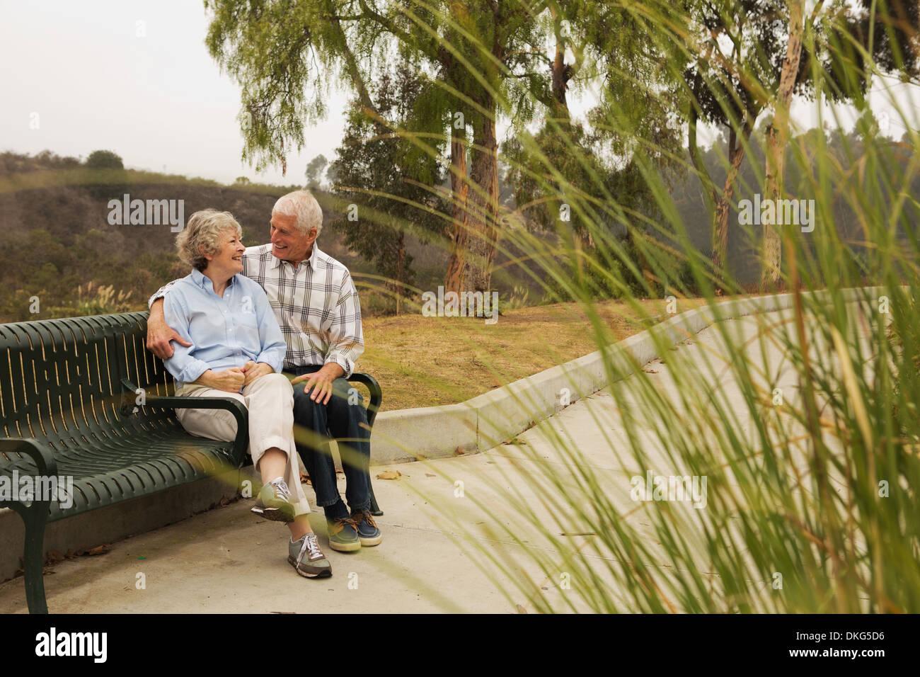 Mari et femme chat amoureusement sur banc de parc Photo Stock