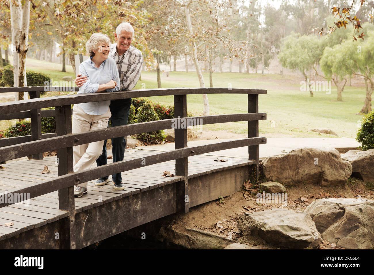 Mari et femme chat amoureusement sur le pont dans le parc Photo Stock