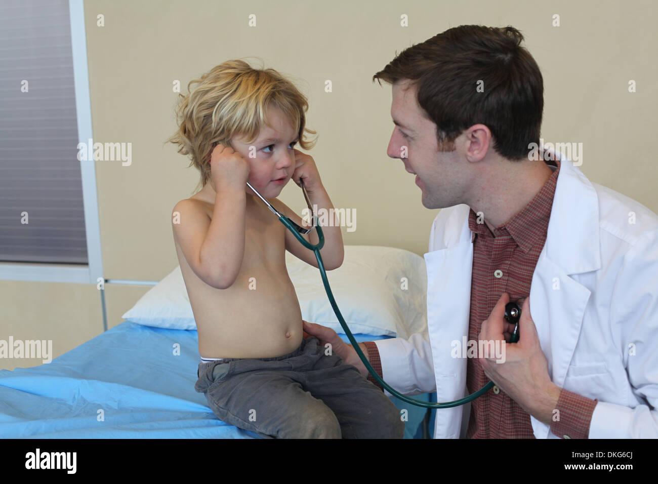 Jeune homme médecin en clinique partager stéthoscope avec boy Photo Stock
