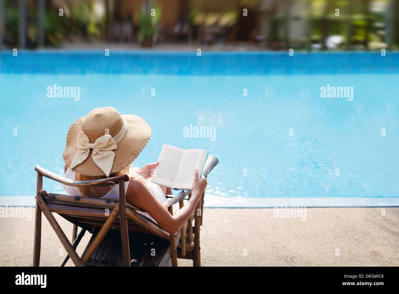 Femme lisant et relaxant près de piscine de luxe Photo Stock