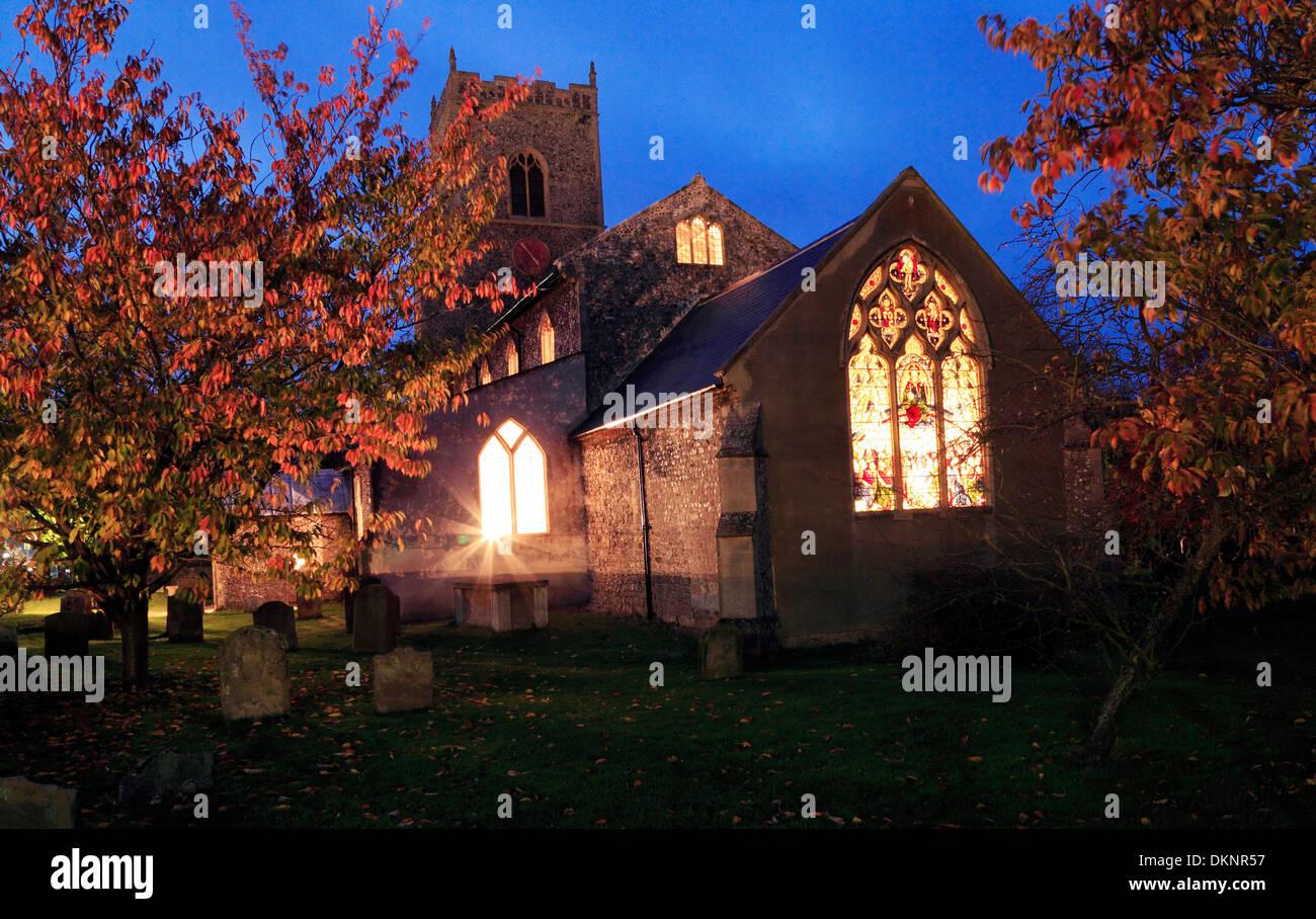Brancaster, lumières de l'Église vitrail lumineux à travers la nuit, Norfolk, Angleterre, Royaume-Uni Photo Stock